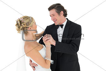 Bride and groom dancing over white background