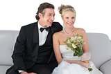 Happy bride sitting with groom on sofa over white background