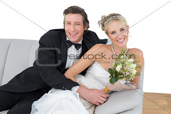 Bride and groom with flower bouquet sitting on sofa