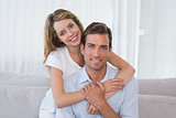 Loving young woman embracing man at home