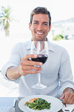 Smiling young man with wine glass having food