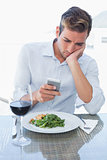 Young man text messaging at food table