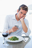 Man text messaging at food table
