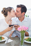 Couple kissing as they hold wine glasses at food table
