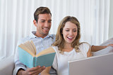 Relaxed loving young couple with book and laptop