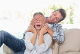 Man covering happy womans eyes in living room