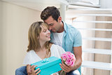 Couple with flowers and gift box sitting on stairs