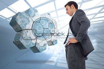 Composite image of stern businessman standing with hands on hips