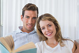 Relaxed young couple reading book at home