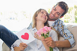 Loving couple with flowers and greeting card