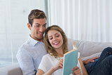 Young couple reading book on couch