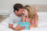 Smiling young couple with gift box in bed