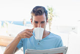 Man drinking coffee and reading newspaper