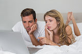 Couple using laptop in bed at home