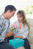 Couple with flowers and gift box sitting on sofa