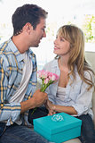 Loving couple with flowers and gift box sitting on sofa