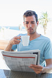 Concentrated man drinking coffee and reading newspaper