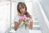 Portrait of a beautiful sad woman with flowers on stairs