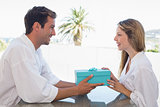 Man giving woman gift box at home