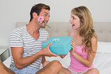 Man giving happy woman a gift box in bed