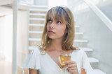 Thoughtful beautiful young woman with wine glass