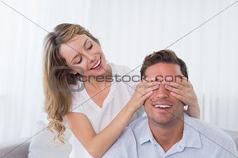 Young woman covering mans eyes