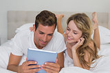 Smiling relaxed couple using digital tablet in bed