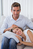 Happy woman resting on mans lap on couch