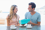Man giving woman gift box at breakfast table