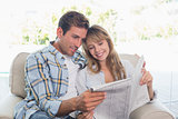 Happy couple reading newspaper on couch