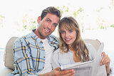 Loving happy couple reading newspaper on couch