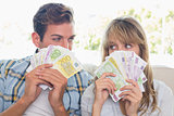 Close-up of a young couple holding Euro notes