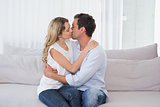 Loving couple sitting and kissing on couch