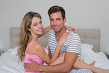 Happy relaxed young couple sitting in bed