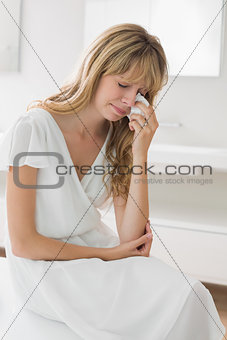 Sad young woman crying in bathroom