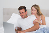 Relaxed smiling couple using laptop in bed