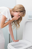 Young woman about to vomit into a toilet