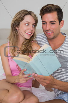 Relaxed young couple reading book in bed