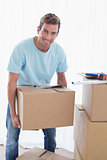 Smiling man with cardboard boxes in new house
