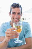 Smiling young man holding wine glass