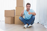 Man gesturing thumbs up with cardboard boxes in new house