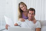 Relaxed couple using laptop on couch