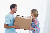 Smiling couple carrying cardboard box in new house