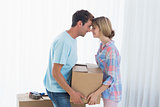 Young couple carrying cardboard box in new house