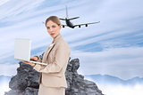 Composite image of businesswoman with a laptop