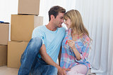 Couple holding new house key against cardboard boxes