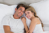 Relaxed young couple together in bed