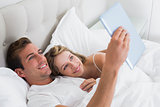 Relaxed couple using digital tablet on couch