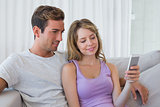 Relaxed couple text messaging on couch