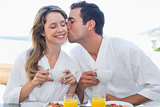 Man kissing woman at breakfast table